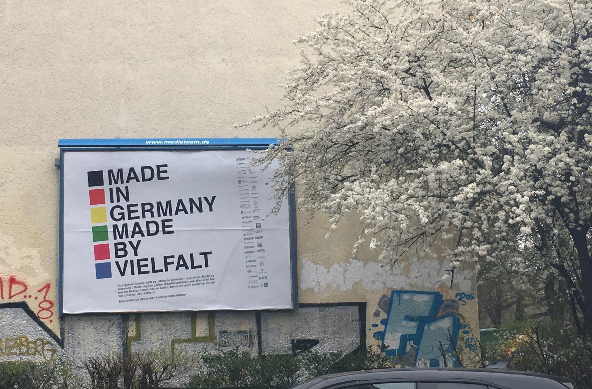 """Plakat mit Aufschrift """"Made in Germany, made by Vielfalt"""" neben blühendem BaumBaum"""